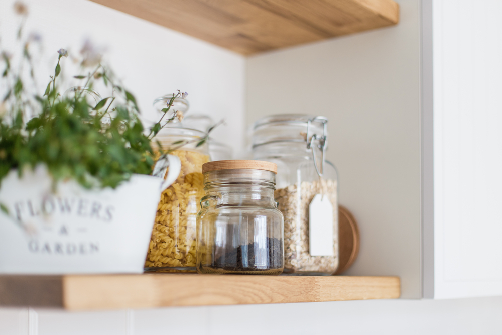 A pantry shelf with a potted plant next to glass jars