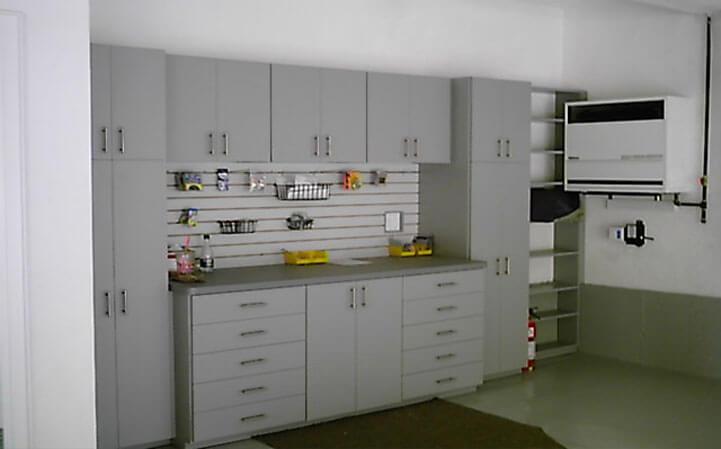 Gray flat panel garage cabinets with workbench and slatwall organization