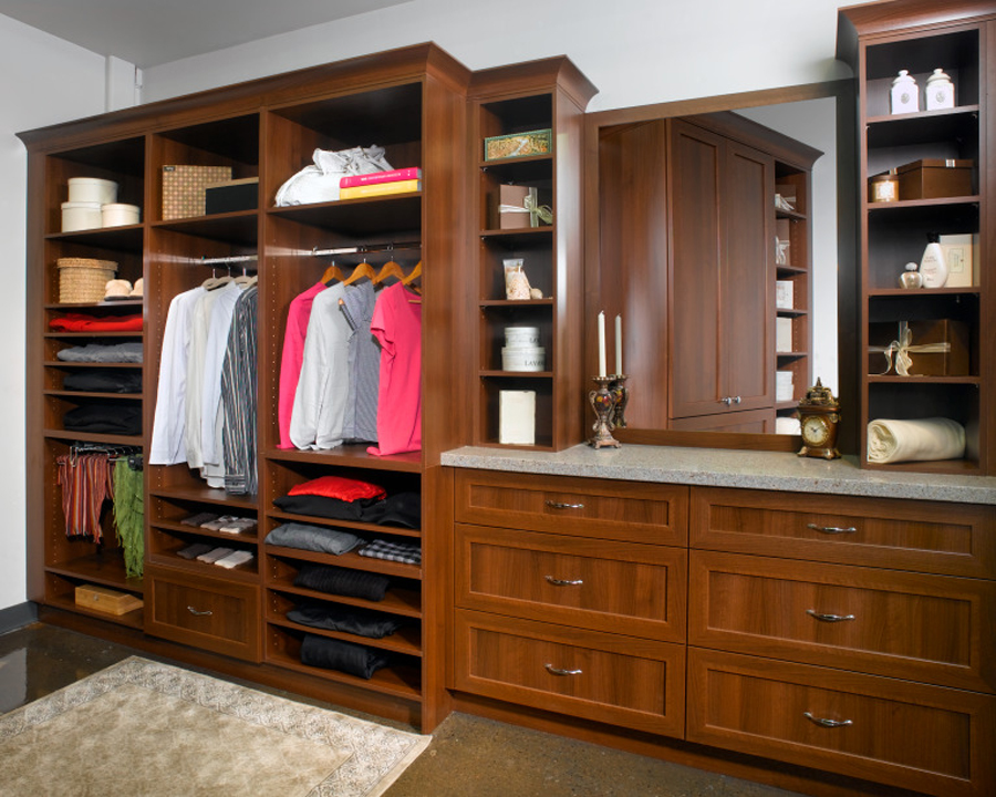Custom open bedroom closet with drawers and countertop