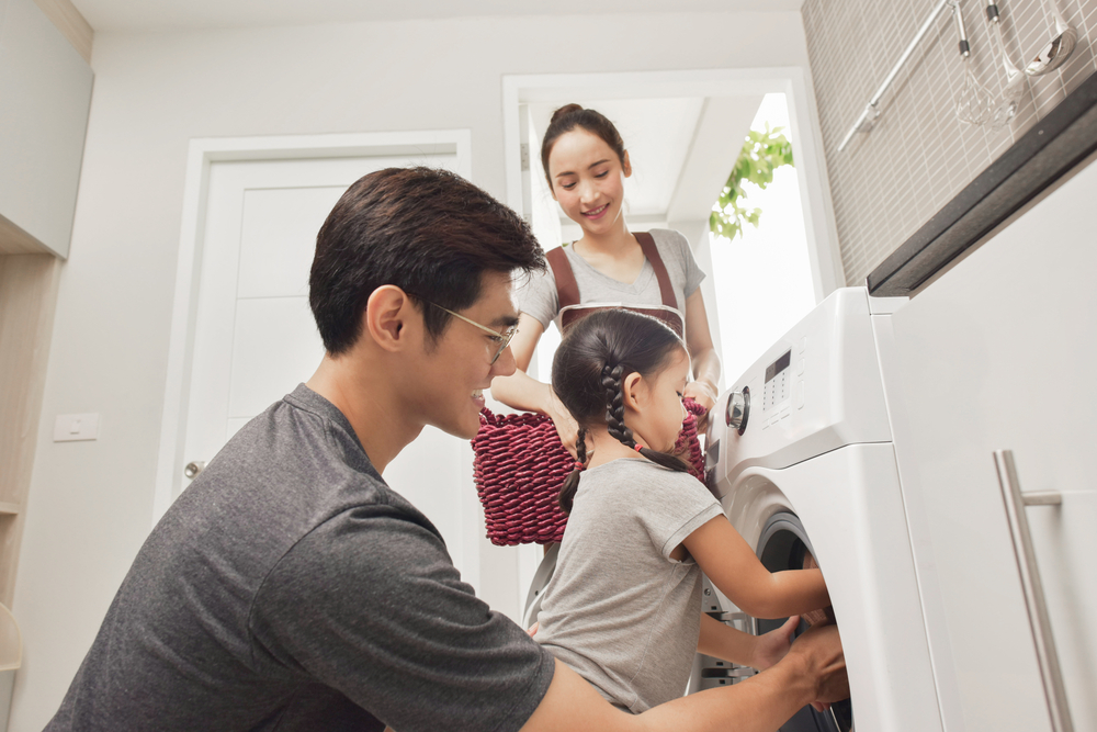 Happy family does laundry in an organized space