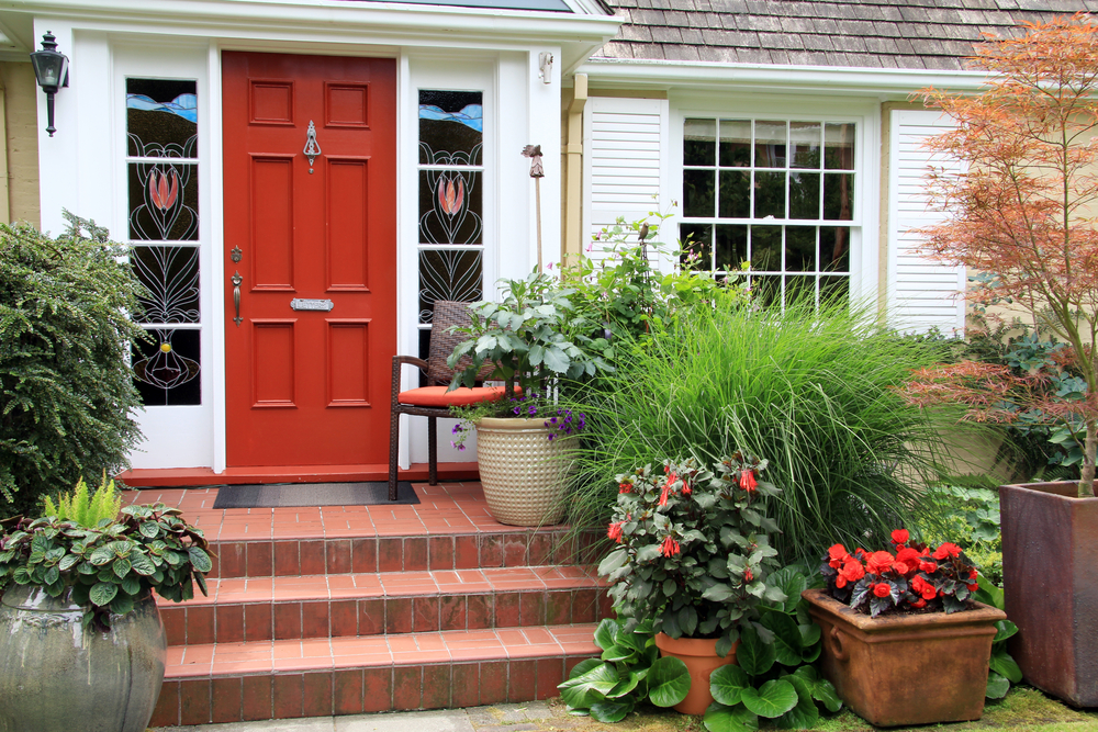 Small Boston home with red front door and lush greenery