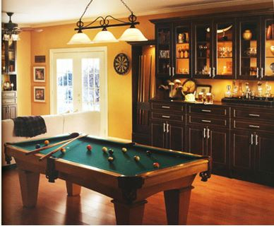 Man cave with pool table in front of backlit liquor cabinet