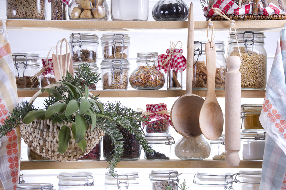 Pantry containing clear jars with various pasta and dried shelf stable foods.
