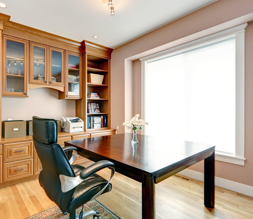 Organized home office with a built-in office cabinet system.