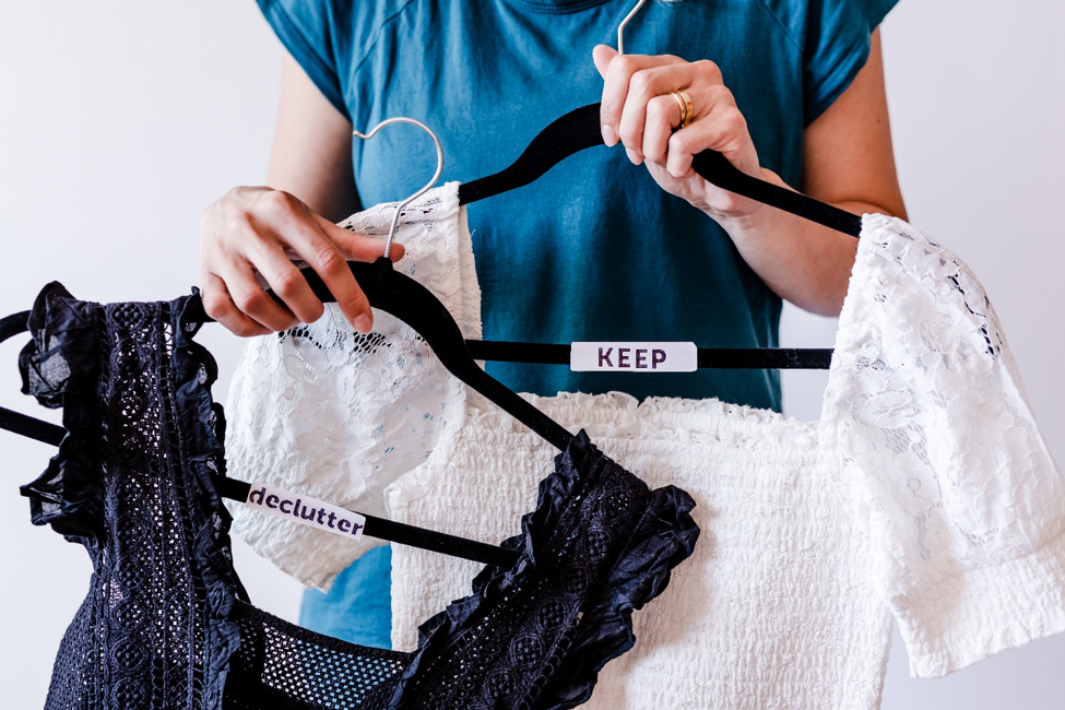"woman in blue shirt holding two articles of clothing on hangers, one labeled ""declutter"" and the other ""keep"""